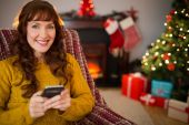 Happy redhead using mobile at christmas — Stock Photo