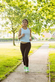 Woman jogging through the park — Stock Photo