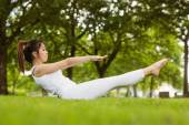 Woman doing boat pose in park — Stock Photo