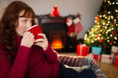 Pretty redhead drinking hot drink at christmas — Stock Photo