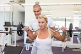 Trainer helping woman with lifting barbell in gym — Stock Photo