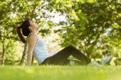 坐在公园的草地上的女人 — 图库照片