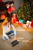 Redhead woman sitting on floor using laptop at christmas — Stock Photo