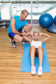 Trainer assisting woman with abdominal crunches at fitness studi — Stock Photo