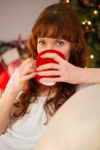 Pretty redhead sitting on couch drinking hot chocolate — Stock Photo