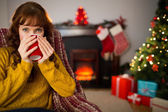 Cheerful redhead drinking hot drink at christmas — Foto de Stock