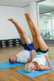 Sporty couple doing pilate exercises at fitness studio — Stock Photo