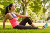 Cheerful fit brunette day dreaming on the grass  — Stock Photo