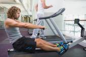 Fit young man on fitness machine at gym — Stock Photo