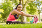 Happy brunette in sportswear stretching on the grass — Stock Photo