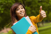 Student with books gesturing thumbs up — Stock Photo