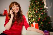 Pretty redhead sitting on the couch phoning — Stockfoto