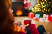 Redhead enjoying coffee on the armchair at christmas — Stock Photo