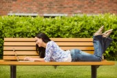 Cool brunette lying on bench using laptop — Stock Photo