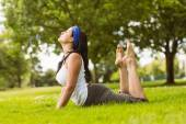 Calm brown hair doing yoga on grass — Photo