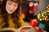 Calm redhead reading a book at christmas — Stock Photo