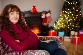 Pretty redhead in jumper sitting on the armchair at christmas — Stock Photo