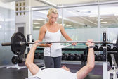 Trainer helping man with lifting barbell in gym — Stok fotoğraf