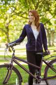 Pretty redhead with her bike — Stock Photo
