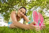 Smiling brunette in sportswear stretching on the grass — Stock Photo