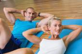 Sporty couple doing abdominal crunches at fitness studio — Stock Photo