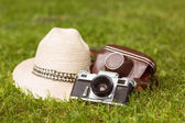 Vintage camera with his cover near a straw hat — Stock Photo