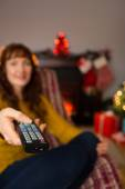 Woman changing channels with remote control at christmas — Stock Photo