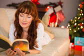 Pretty woman lying on a cosy couch reading book — Stock Photo