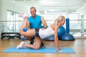 Trainer assisting woman with exercises — Stock Photo
