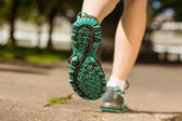 Woman in running shoes jogging on path — Stock Photo