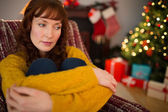 Thoughtful redhead sitting on the armchair at christmas — Stock Photo