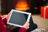 Woman in jumper using tablet at christmas — Stock Photo