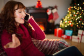 Smiling redhead phoning and gesturing at christmas — Stock Photo