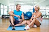 Fit couple sitting on floor at fitness club — Stock Photo