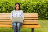 Smiling brunette sitting on bench using laptop — Stock Photo