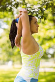 Focused fit brunette stretching in the park — Stock Photo
