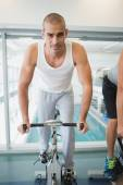 Handsome man working out on exercise bike at gym — Stock Photo