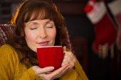 Beautiful redhead enjoying hot drink at christmas — Stock Photo