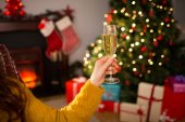 Redhead holding glass of champagne on couch at christmas — Foto de Stock