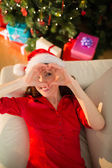 Smiling redhead making heart with her hands — Stockfoto