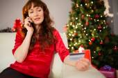 Redhead on the phone holding credit card — Stock Photo