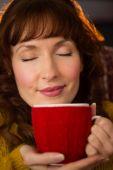 Portrait of redhead enjoying hot drink at christmas — Stock Photo