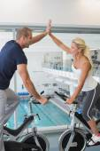 Couple giving high five on exercise bikes — Stock Photo