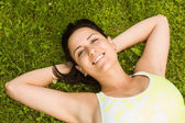 Relaxed fit brown hair lying on grass — Stock Photo