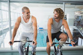 Fit men working on exercise bikes at gym — Foto de Stock