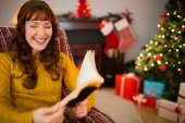 Happy redhead reading on the armchair at christmas — Stock Photo