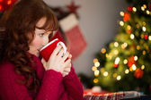 Beautiful redhead drinking hot drink at christmas — Stock Photo