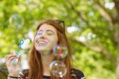 Woman blowing bubbles at park — Stock Photo