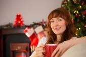 Smiling redhead holding a mug of hot drink at christmas — Stock Photo