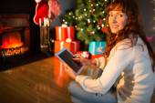 Redhead woman sitting on floor using tablet at christmas — Fotografia Stock